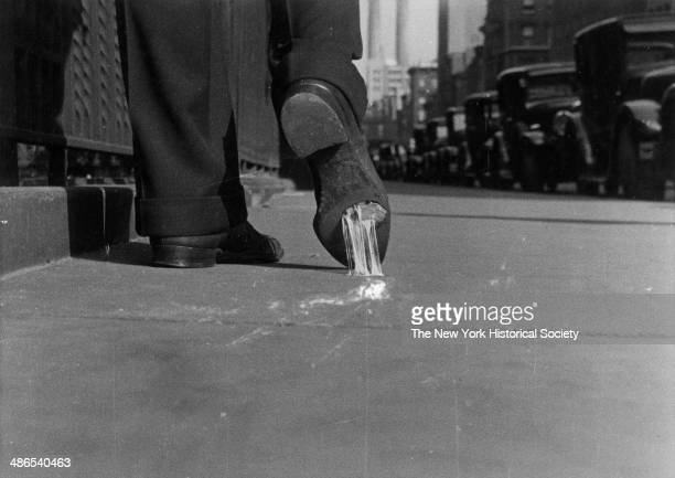 Closeup view of a man walking on a city sidewalk with chewing gum stuck on the bottom of his shoe New York 1930
