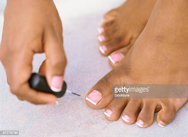 close-up view of a person applying nail varnish on toe nails - pretty toes and feet stock photos and pictures