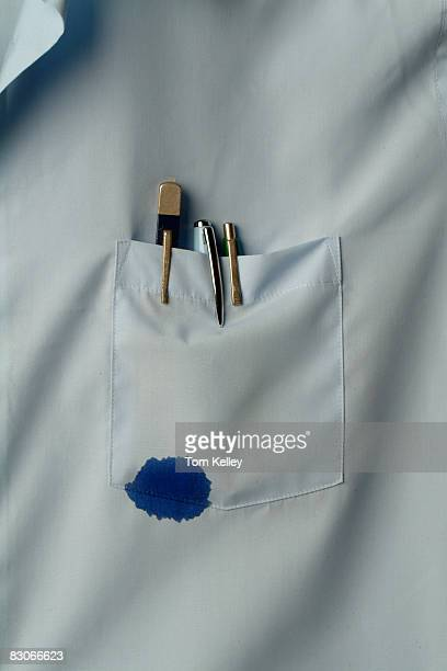 Closeup view of a shirt pocket that holds several pens one of which leaks blue ink California 1970s