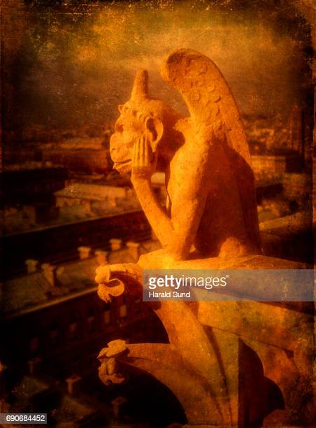 Closeup view of a stone figured dragon gargoyle on the Notre Dame Cathedral in Paris, France.  d
