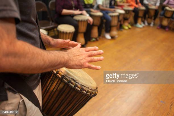 Closeup view of a teacher's hands as he plays his djembe during a drum circle workshop Rockland County New York June 9 2016