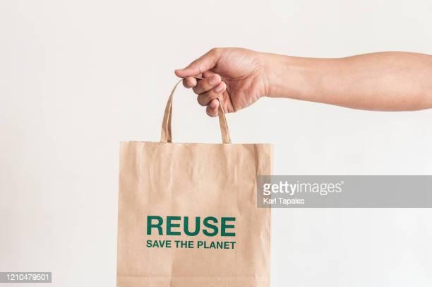"""a close-up view of a young person holding a paper bag with phrase saying: """"reuse, save the planet"""" on a white background - bag photos et images de collection"""