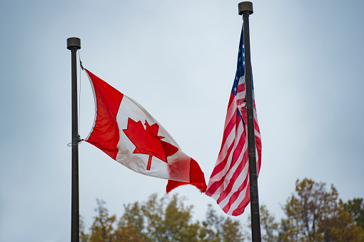 Close-up view of an American flag and a Canadian flag waving in the wind. 1089160346
