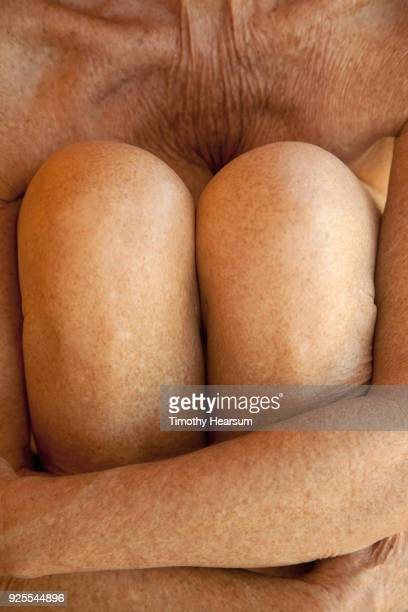 Close-up view of an older woman's arms wrapped around her knees as she pulls them to her chest