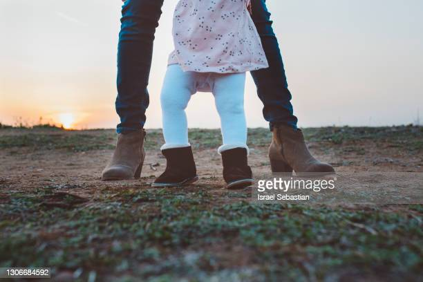 close-up view of an unrecognisable mother teaching her baby to take his first steps. - beginnings stock pictures, royalty-free photos & images