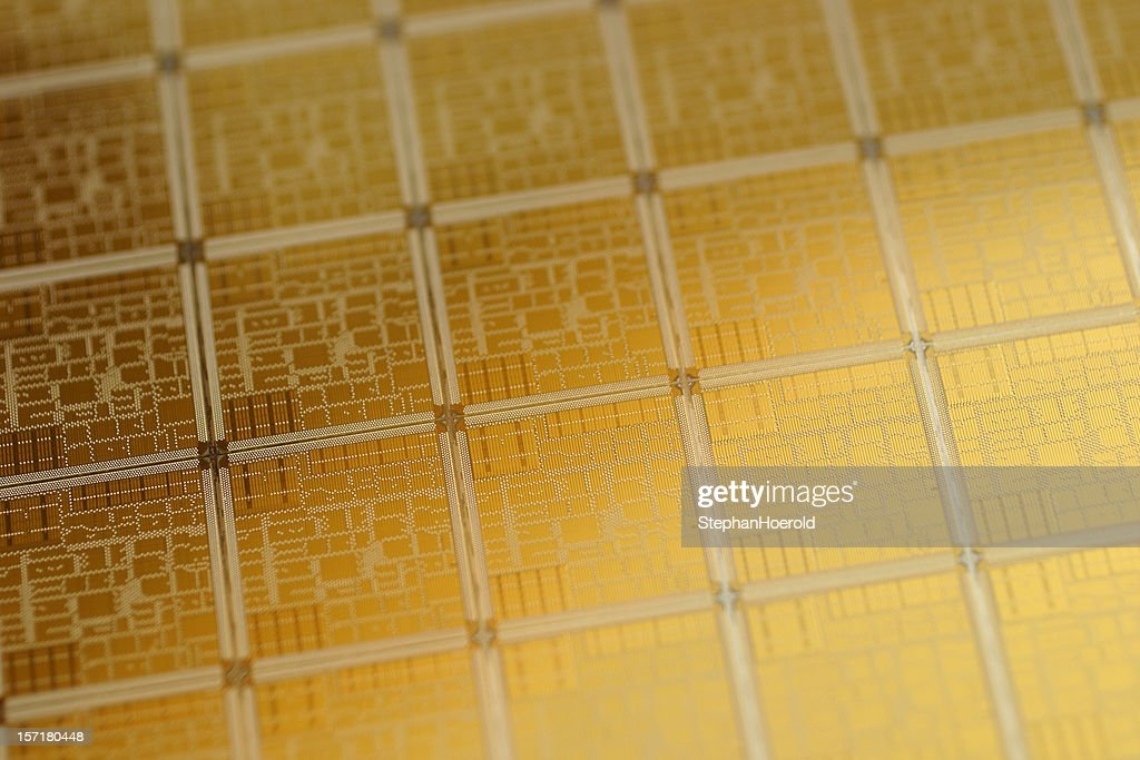 Close-up view of chip wafer with regular pattern in gold : Stock Photo