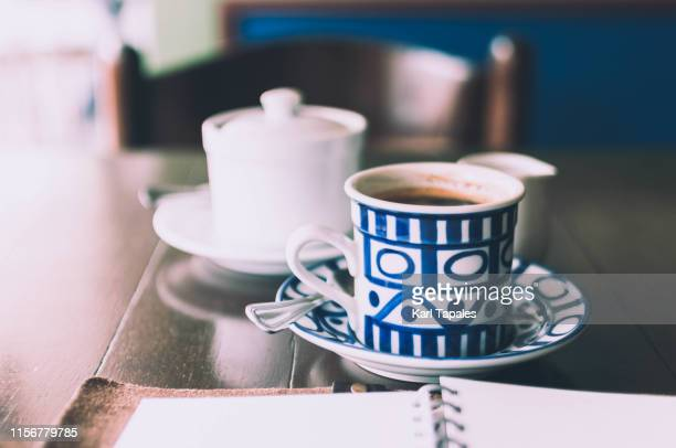 a close-up view of coffee cup on a wooden table - coffee table stock pictures, royalty-free photos & images