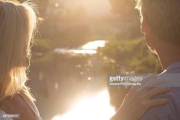Close-up view of couple looking up creek, sunrise
