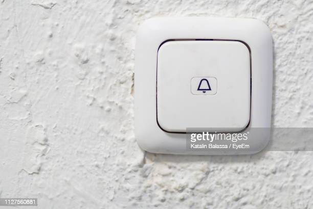 close-up view of door bell on wall - doorbell stock pictures, royalty-free photos & images