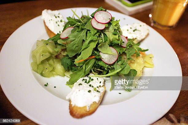 Close-Up View Of Fresh Salad And Baguette Bites On White Plate