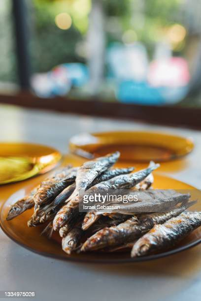close-up view of freshly grilled sardines on orange glass plate and marble table. healthy food concept. - オキスズキ ストックフォトと画像
