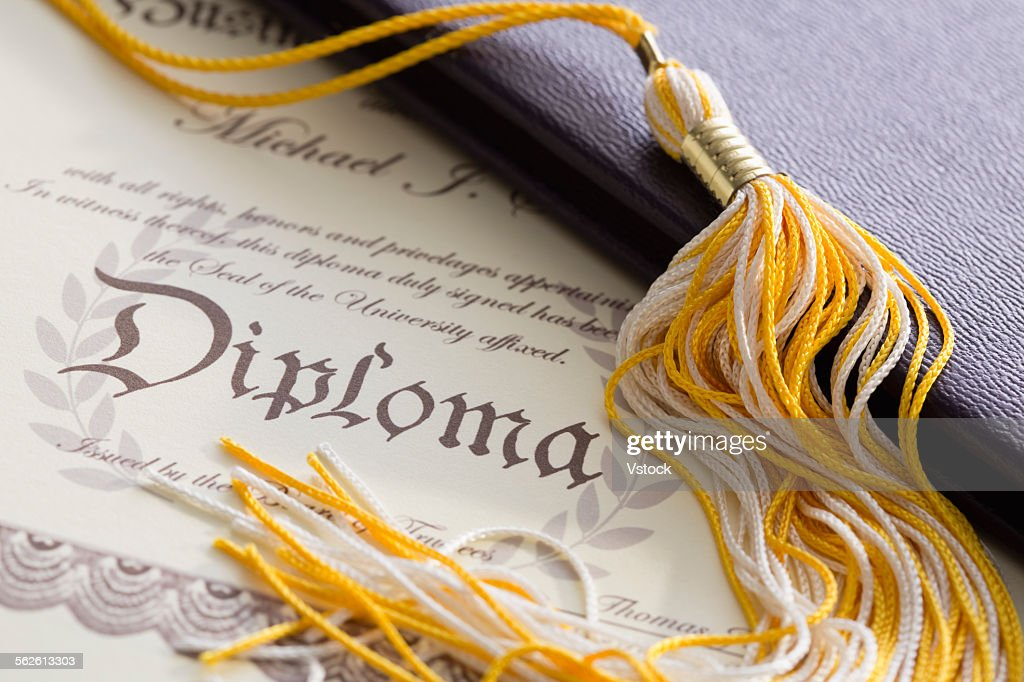 Close-up view of graduation tassel and diploma : Stock Photo