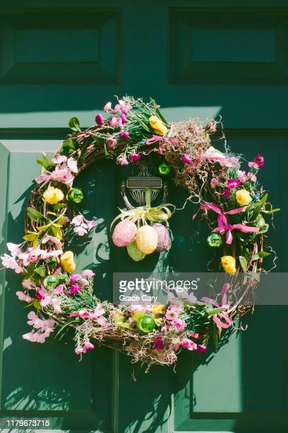 close-up view of green front door with easter wreath - easter stock pictures, royalty-free photos & images