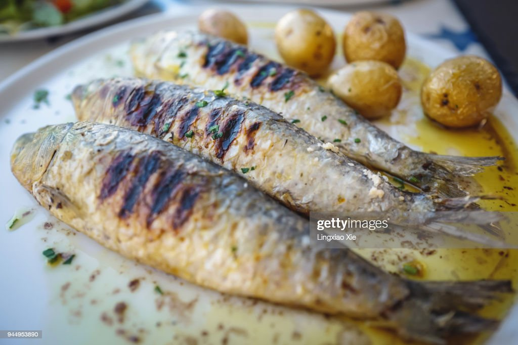 Close-up view of grilled sardine fishes served in oil with baked potatoes, Portugal : Stock Photo
