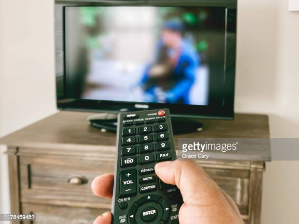 close-up view of hand pointing remote control at tv - flat screen stock pictures, royalty-free photos & images