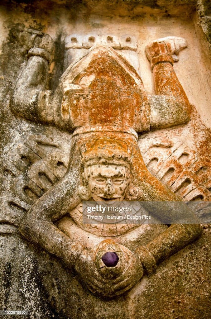 Close-up view of human figure splayed like a toad and holding a purple stone, carved on the side of a Mayan ruin : Stock Photo