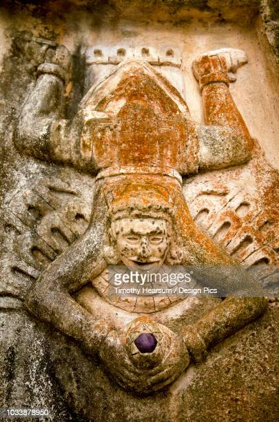 Close-up view of human figure splayed like a toad and holding a purple stone, carved on the side of a Mayan ruin