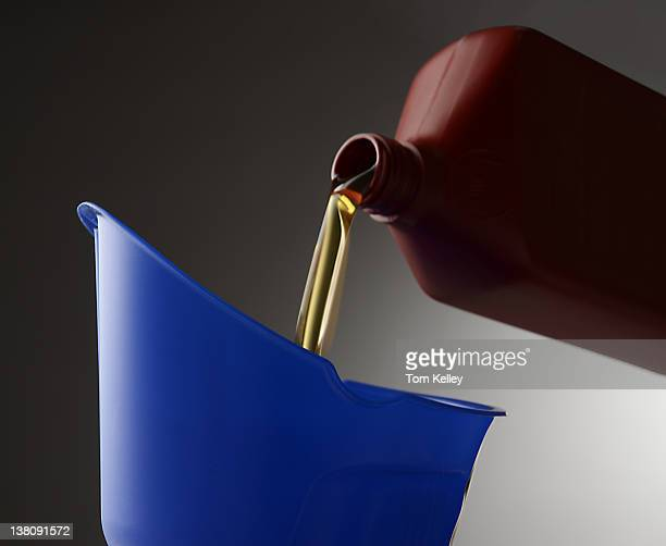 Closeup view of motor as it is poured from a red container into a blue bucket September 29 2011