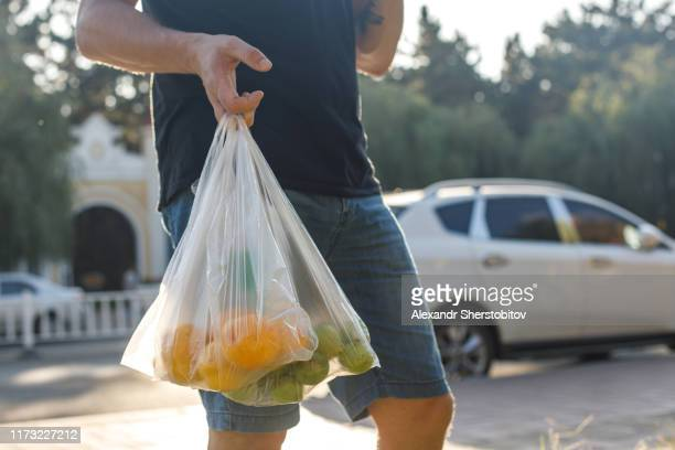 close-up view of plastic store bag with fruits in human hand. street morning market in china - ビニール袋 ストックフォトと画像