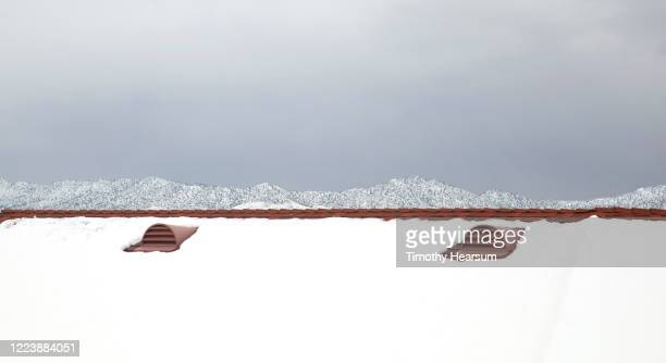 close-up view of red shingled roof; snow covered ridge of mountains and cloudy sky beyond - timothy hearsum stock pictures, royalty-free photos & images