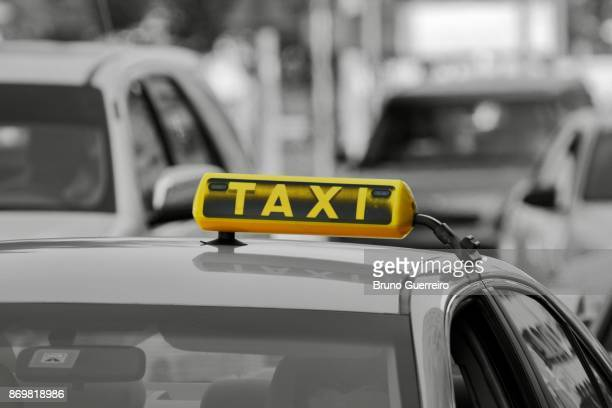 Close-up view of taxi sign against blurred traffic