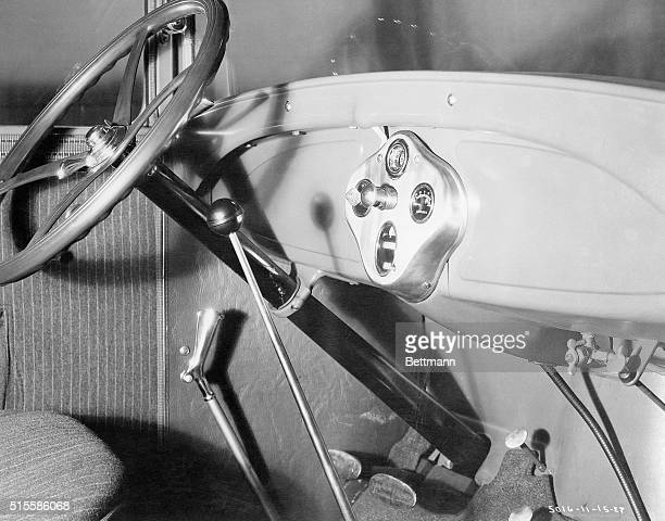 A closeup view of the interior of the new Ford car shows the improved instrument panel steering wheel with lighting switch in the center and the gear...