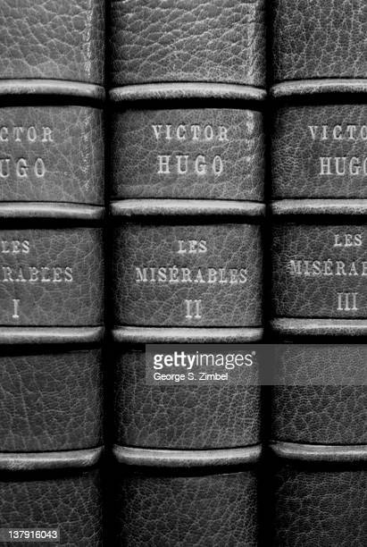 Closeup view of the spines of a three volume leatherbound edition of Victor Hugo's 'Les Miserables' mid twentieth century