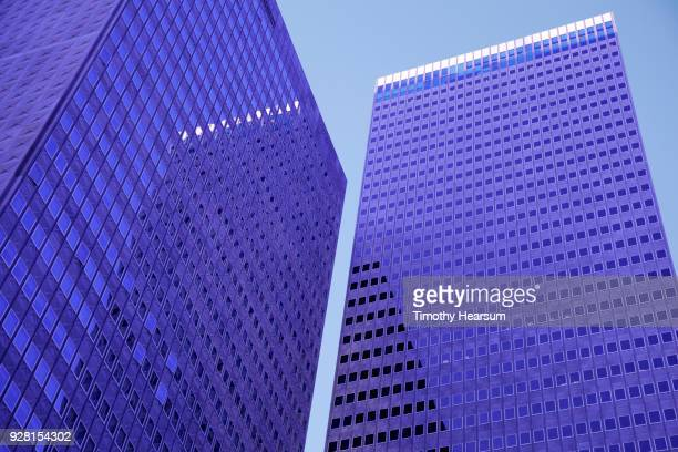Close-up view of two city skyscrapers with reflections against a blue sky