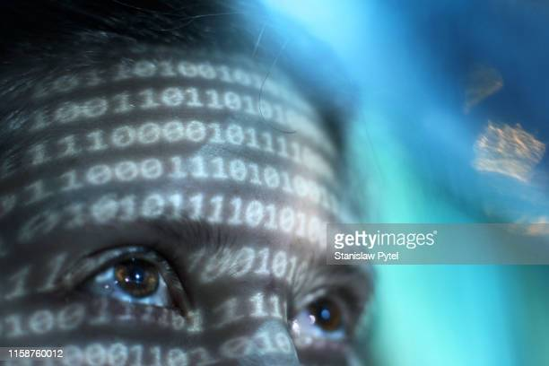 closeup view of womans face lit by binary code - big data white stock pictures, royalty-free photos & images