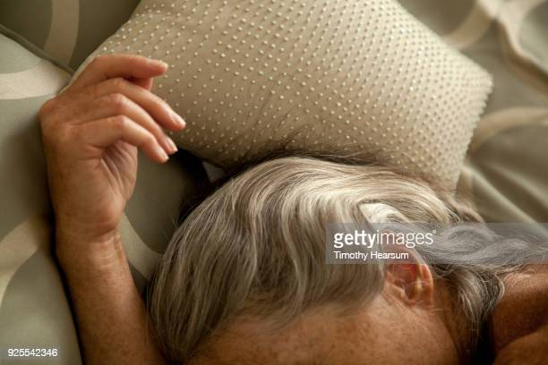 Close-up view of woman's hand and streaked gray hair against sequined pillow and comforter