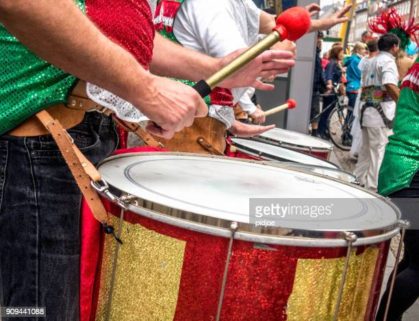 close-up view of young male drummers playing in a street marching band during a samba parade in santiago de compostela, galicia, spain. - mardi gras party stock photos and pictures