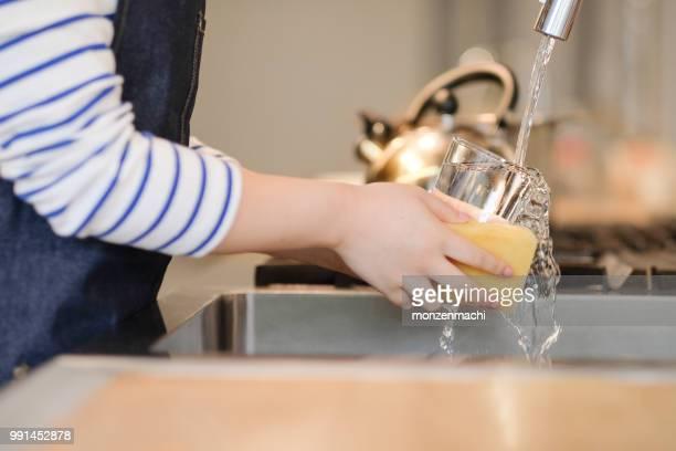 クローズ アップ ウェイトレスさんの手のレストランの台所でガラスの洗浄 - 皿洗い ストックフォトと画像