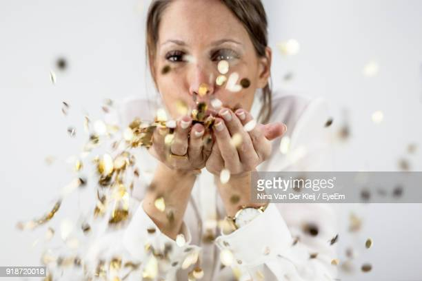 Close-Up Woman Blowing Confetti Against Wall