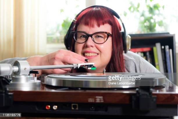 close-up woman listening to records on the floor - cat's eye glasses stock pictures, royalty-free photos & images