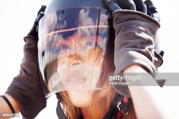 close-up woman looking away while wearing crash helmet - crash helmet stock pictures, royalty-free photos & images