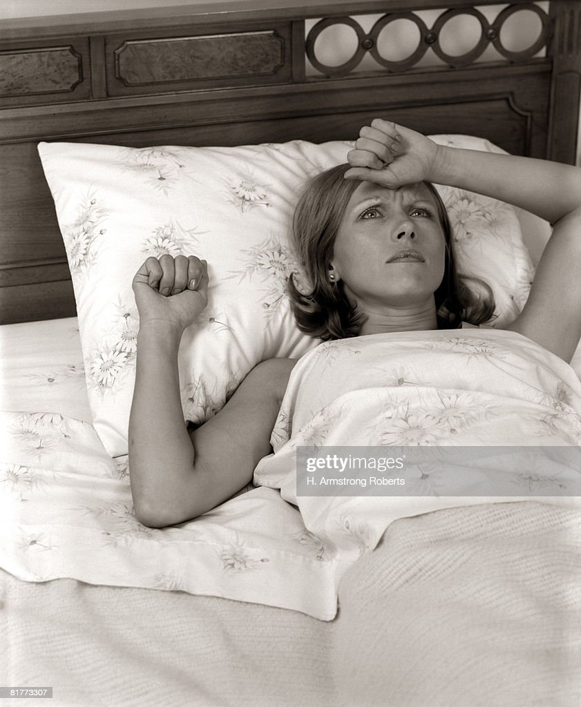 Close-Up Woman Lying In Bed With Pained Expression Holding Hand To Forehead Indoor. : Stock Photo