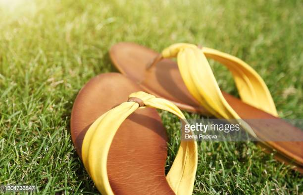 close-up yellow flip-flops on green grass - open toe stock pictures, royalty-free photos & images