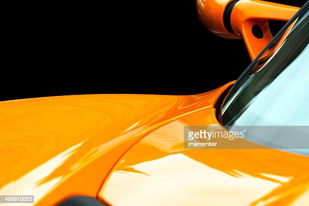 Closeup yellow Lotus car bonnet against black background, copy space