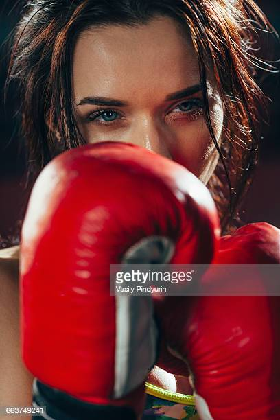 Close-up young female boxer at gym