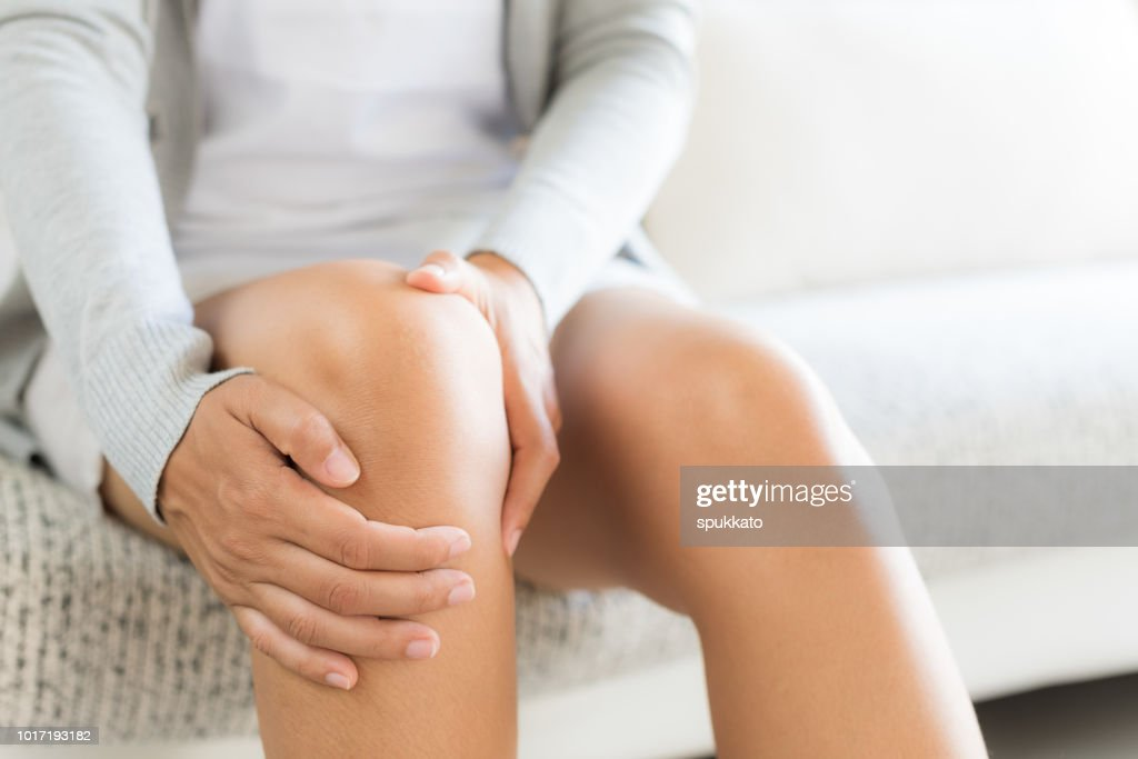Closeup young woman sitting on sofa and feeling knee pain and she massage her knee at home. Healthcare and medical concept. : Stock Photo