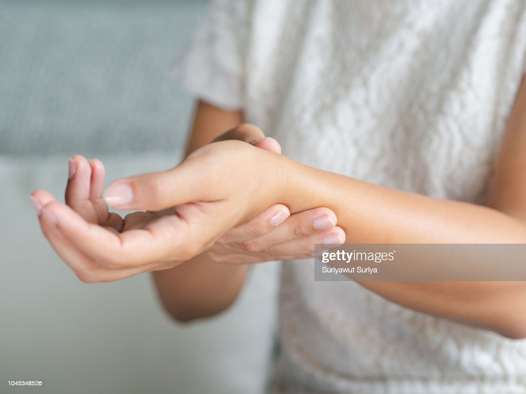 Closeup young woman sitting on sofa holds her wrist. hand injury, feeling pain. Health care and medical concept. : Stock Photo
