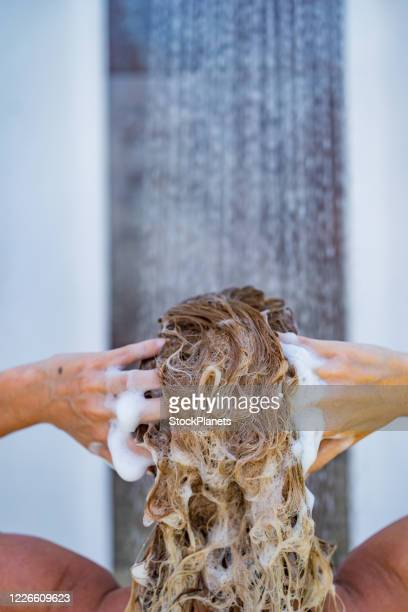 close-up young woman washing hair with shampoo - washing hair stock pictures, royalty-free photos & images
