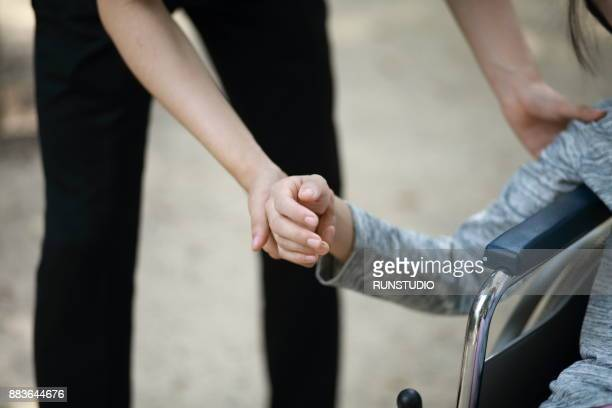 Close-up,doctor's hand holding woman's hand in wheelchair, supporting care concept