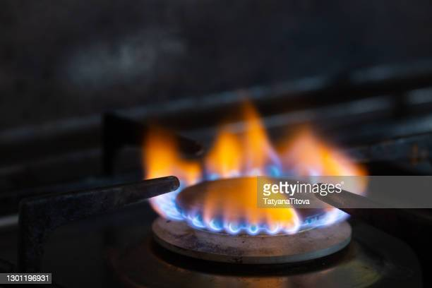 closeups of a natural gas stove flame on dark background - butane stock pictures, royalty-free photos & images