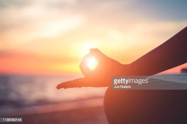 close-up,silhouette mid adult woman meditating at beach against clear sky during sunset - 無の境地 ストックフォトと画像