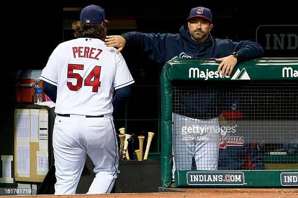 Closing pitcher Chris Perez gets a pat on the back from pitching coach Mickey Callaway of the Cleveland Indians after Perez left the game during the...