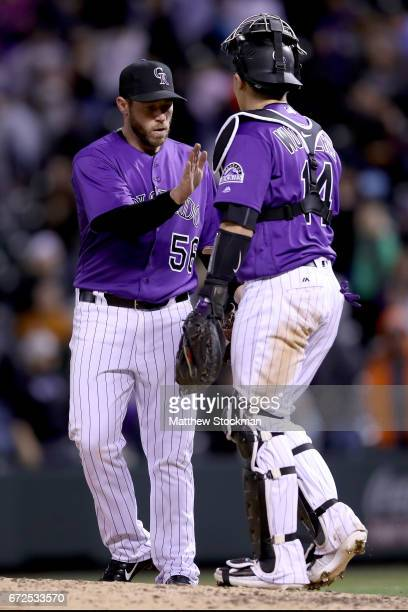 Closing pitcher Greg Holland and catcher Tony Wolters of the Colorado Rockies celebrate their win over the Washington Nationals at Coors Field on...