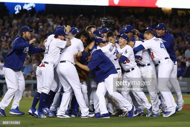 Closing pitcher Kenley Jansen of the Los Angeles Dodgers is mobbed by his teammates after their 42 win in an MLB game against the San Francisco...