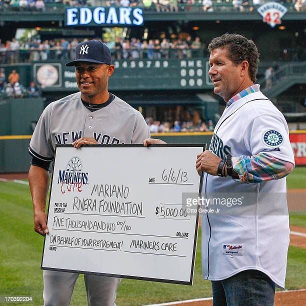 Closing pitcher Mariano Rivera of the New York Yankees accepts a gift on behalf of the Seattle Mariners from former Mariners' great Edgar Martinez...