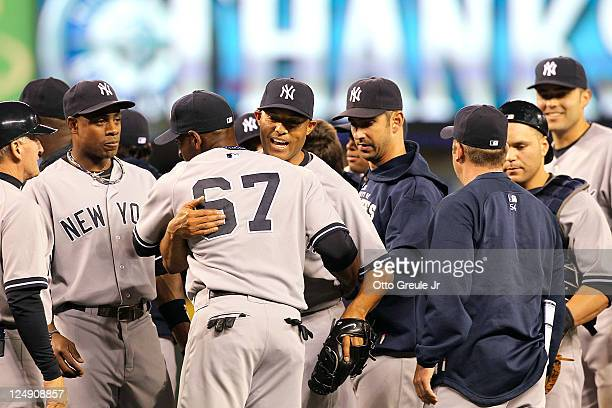 Closing pitcher Mariano Rivera of the New York Yankees is congratulated by teammates after defeating the Seattle Mariners 32 at Safeco Field on...